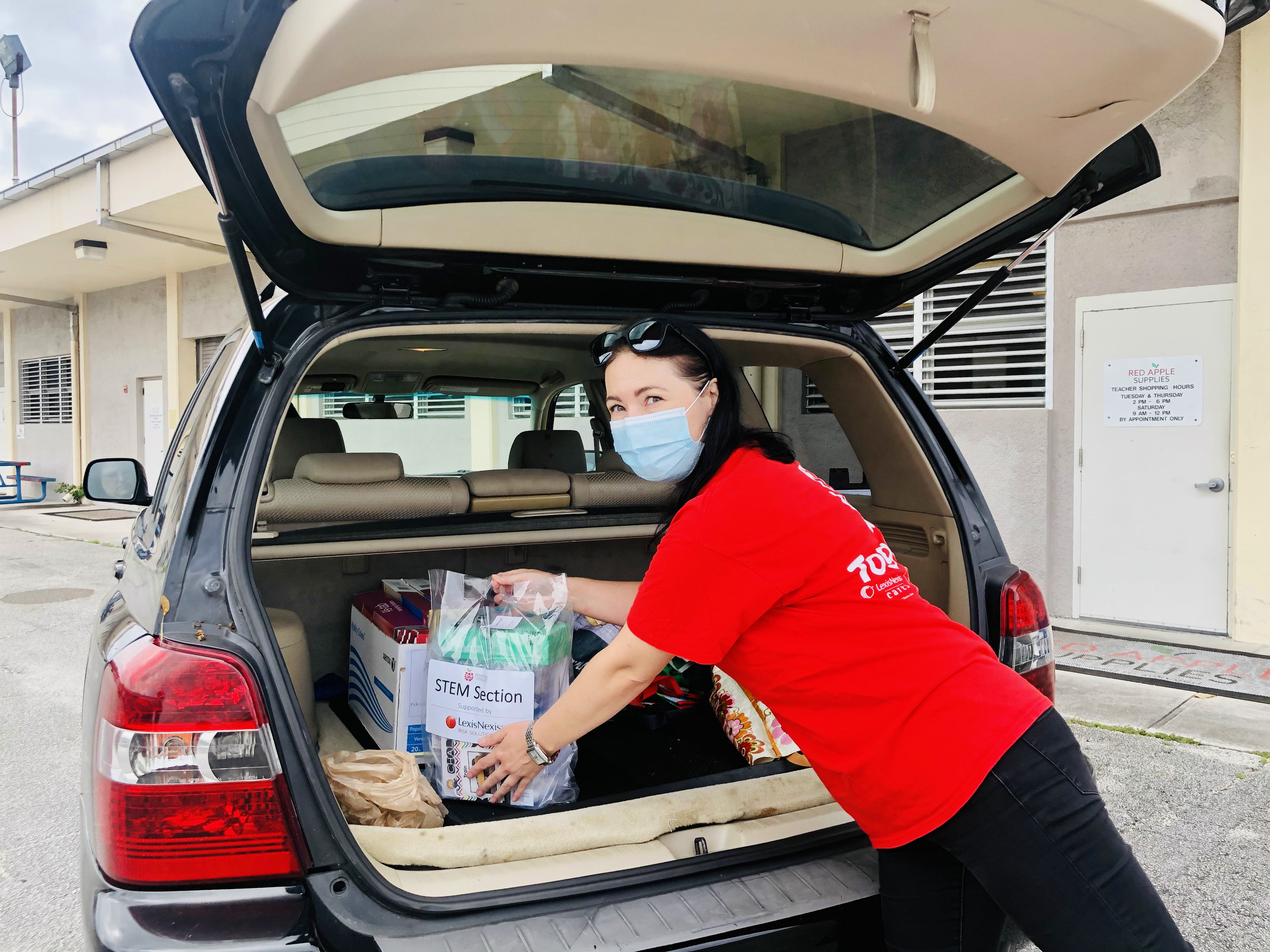 LexisNexis Risk Solutions volunteer places STEM kit in teacher's car
