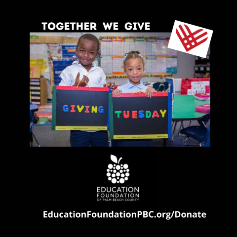 Two Students holding a Giving Tuesday sign in a classroom
