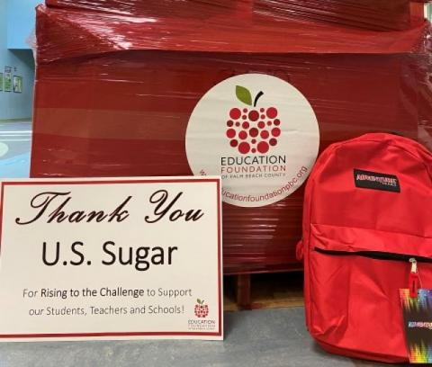 A pallet of supplies and backpack with a sign of thanks to US Sugar for support